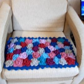 Коврик Островок из разноцветных, связанных спицами цветочков